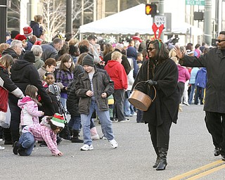 JESSICA M. KANALAS | THE VINDICATOR..Sixth ward council woman Janet Tarpley passes candy out with her fiance, David Portis, during the holiday parade in Downtown Youngstown.