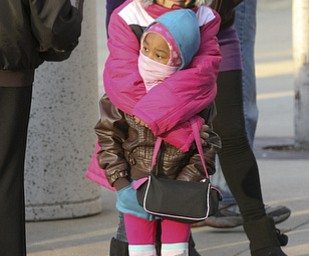 JESSICA M. KANALAS | THE VINDICATOR..Ziyah Rivera, 10, holds her sister, Morgan Jackson, 4, of Youngstown for warmth during the holiday parade in Downtown Youngstown.