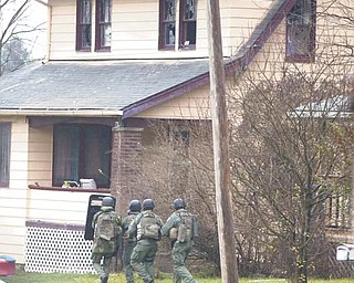 Ohio State Highway Patrol Special Response Team members approach the Girard home where Keith Jornigan was found dead. Early Monday, Jornigan reportedly shot his wife with a crossbow and beat her with a bat at their home in Bristol before leading police on a 20-mile chase to Girard.