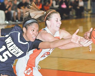 Howland's Taylor Ginnis battles Anita Brown (15) of Warren Harding for a loose ball during Monday's basketball game. The Tigers won 58-47.