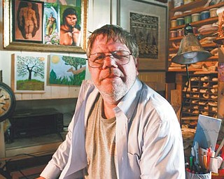 Scott Pergande, above, sits in his art studio in his Youngstown home. Pergande was attacked outside his home in August and lost the vision in his left eye. He will auction art from his collection Sunday to help pay his medical bills.