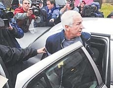 Former Penn State associate head football coach Jerry Sandusky is escorted to a police car Wednesday in Bellefonte, Pa., after being arrested on new child-sex abuse charges brought by two new accusers.