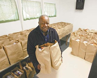 The Rev. Harold Logan, pastor of Beulah Baptist Church, 570 Sherwood Ave., Youngstown, loads two of the 200 bags of food the church's Operation Food Basket expects to distribute to needy Youngstown-area residents Saturday from 10 a.m. to 1 p.m.
