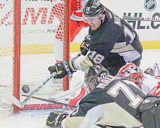 Pittsburgh Penguins' James Neal (18) and Evgeni Malkin (71) try to get the puck past Detroit Red Wings goalie Jimmy Howard in the second period of a game Tuesday in Pittsburgh. Howard made the saves, and the Penguins did not score.