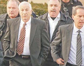 Former Penn State University assistant football coach Jerry Sandusky, second from left, walks with his attorney, Joe Amendola, second from right, as he leaves the Centre County Courthouse in Bellefonte, Pa., on Tuesday.