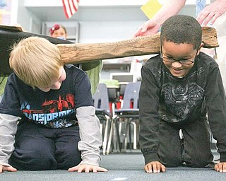 Austin Shanabarger and Nolan Ballard of Watson Elementary School in Austintown try out an oxen yoke as they get a hands-on lesson about pioneer life. Ester Hallaman, volunteer with the Arms Family Museum of Local History, is sharing a story and artifacts during her two-day visit to the school.