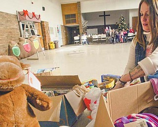 Mindy Jones, a volunteer at the Warren Family Mission on Elm Road, sorts through toys for needy children.
