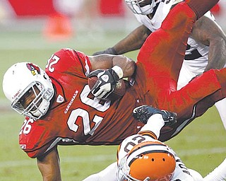 Arizona Cardinals running back and former Ohio State standout Beanie Wells (26) is upended by Cleveland Browns free safety Mike Adams (20) and D'Qwell Jackson (52) in the second half Sunday's NFL game in Glendale, Ariz. The Browns gave up a 10-point lead and fell to the Cardinals, 20-17, in overtime.