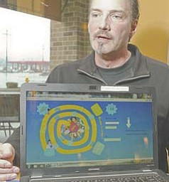 Gary Downing of Cortland displays Brain Swaggle, the interactive computer board game he developed, which combines the vocabulary skills needed for Scrabble with the strategic skills required for chess.