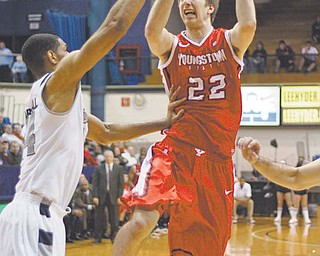 YSU forward Cale Zuiker tries to maneuver around Akron center Zeke Marshall during Monday's game at
