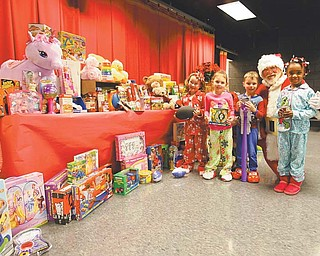 Struthers Elementary School kindergartners Hannah Johnson, left, Emma Bailey, Kamerion Nash and Tattiaunna Holmes show off the toys and food the school gathered for the Rescue Mission of the Mahoning Valley and Neighbors Helping Neighbors. The school presented the donations to Santa on Thursday morning after he arrived at the school on a firetruck.