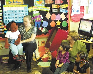 "Shown above are Kristen Hartz-McCleery of the D&E Counseling Center, and Wally, a child-sized puppet, teaching preschoolers at Easter Seals in Youngstown. She is assisted by DeLynn Logan of PNC Bank. The counseling center recently received a $10,000 grant from The PNC Foundation, allowing them to provide its Dina Dinosaur program to two preschool classrooms. Hartz-McCleery uses Wally to ""talk"" to kids about proper behavior, following rules, friendship and other topics. The program is one of several offered by the center's UPSTREAM Early Child Services designed to help children ages 2 to 8 grow resiliency and emotional health."