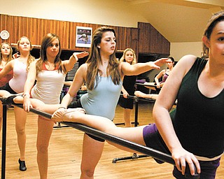 From front to back, Amanda Joerndt of Boardman, Sarah Bobby of Salem, Amanda Walsh of Youngstown, Shannon Joy of Columbiana and Lexi Marco of Boardman stretch on a barre before practice at Ruth's Robics and Dance Company. The dancers will perform with the musical act Train at the college football Orange Bowl in Florida next Wednesday.