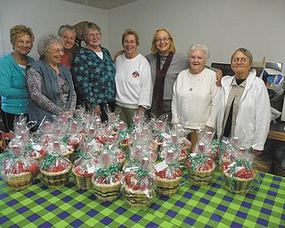 Members of the Youngstown Area Weavers Guild met recently to make baskets for the needy. The hand-woven creations were then filled with personal care items and donated to The Way Station in Columbiana County. Members who helped with the project, left to right: Nancy Marshall; Sally Macklin; Lois Romito; Nina Winchester; Liz Andrazo, guild president; Carolyn Furnish; Mary Furguson; and Felicia MacMillan. The guild also collected gloves and hats for various charities and toys for the local Toys for Tots campaign.