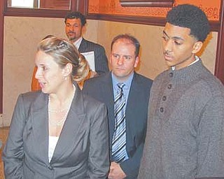 Attorneys Sarah Baker, left, and Tim Pettorini stand with Arthur Cook while answering questions Wednesday in Trumbull County Common Pleas Court. A judge there granted a temporary restraining order allowing Cook to play sports until at least Jan. 13, when a hearing for a preliminary injunction will take place. At rear is Cook's father, Gene Cook Jr.