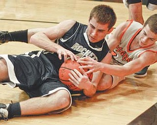 Lowellville's Drew McLaughlin, front, fights for a loose ball with Springfield's Eoghan Bees during the first quarter Wednesday in New Middletown. The Tigers won, 67-36.