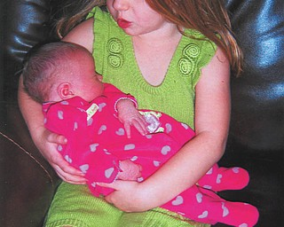 Sarah Katharine Goldner sings a lullaby to her new baby sister, Grace Eleanor. They are the daughters of Bill and Christina Goldner of Westerville and granddaughters of Margie Goldner of Columbiana.