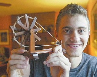 Ben Stoyak holds a replica of a spinning wheel he brought back from a recent trip to India. Stoyak's trip was part of an honors course at the University of Cincinnati in which he traveled for two weeks to villages on the west side of the country and studied the impact of their access to clean water.