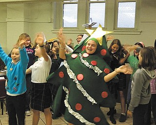 For the third year in a row, girls from Holy Family School's Acts of Random Kindness Club (ARK) sang at the annual holiday meal served at the Immaculate Conception-Sacred Heart of Jesus soup kitchen on Youngstown's East Side. Alena Argiro, grade 7, is dressed as the joyous Christmas tree. As the club performed, visitors were served a meal, various desserts and a beverage.