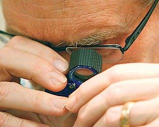 Tom Bartholomew of TeleGold Jewelers in Boardman looks through a magnifier to see the karat marking on a piece of jewelry.