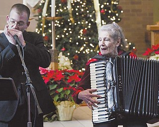 The Rev. Michael Marcelli of St. Charles Church, Boardman, performs Christmas music on his harmonica, accompanied by accordionist Betty Bannon during a Christmas music concert Sunday at the church.