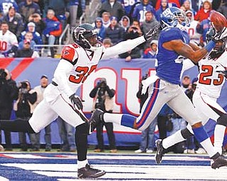 New York Giants wide receiver Mario Manningham, a graduate of Harding High School, pulls in a 27-yard touchdown pass against Atlanta Falcons strong safety James Sanders (36) and Dunta Robinson during the second half of their wild card playoff game Sunday.