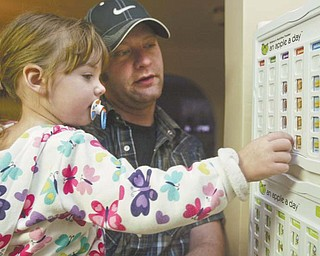 Chloe Baer, 2, and her father Matt Baer, of Poland, log Chloe's healthy eating habits using her An Apple A Day tracking tool. Baer said the program, which he also uses with his 7-year-old daughter, Brianna, helps him keep track of what his children are eating and gets them involved in their own nutrition.