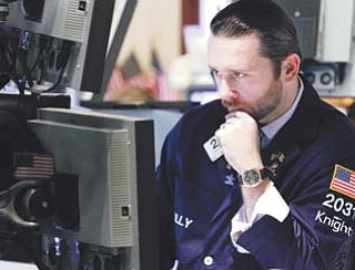 Specialist Christopher Gildea works on the floor of the New York Stock Exchange on Tuesday. U.S. stocks traded solidly higher Tuesday after European markets rallied and corporate bellwether Alcoa predicted stronger demand in 2012.