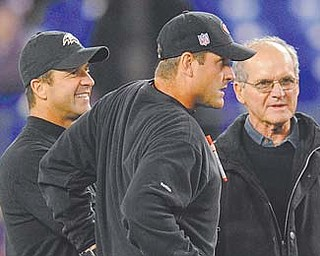 Baltimore Ravens coach John Harbaugh, left, chats with his brother, San Francisco 49ers coach Jim Harbaugh, center, and their father, Jack, before a game in Baltimore. The Harbaughs, separated in age by all of 15 months, have taken different paths to find themselves one win from facing off in the Super Bowl.