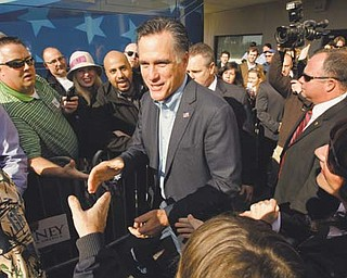 Republican presidential candidate Mitt Romney, center, greets the crowd at his campaign headquarters