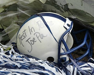 A miniature football helmet lies among flowers left at the foot of a statue of Joe Paterno outside Beaver Stadium on the Penn State University campus after learning of his death Sunday, Jan. 22, 2012 in State College,Pa..  (AP Photo/Gene J. Puskar)