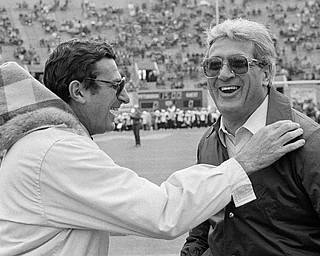 In this Nov. 19, 1983, file photo, Penn State coach, Joe Paterno, left, and Pittsburgh coach Foge Fazio talk before a college football game in Pittsburgh. Fazio, who succeeded Jackie Sherrill ascoach at alma mater Pittsburgh and later was a defensive coordinator for the NFL's Vikings and Browns, died Wednesday night, Dec. 2, 2009, following a lengthy battle with leukemia. He was 71. (AP Photo/Gene J. Puskar, File)