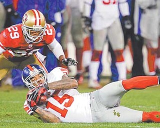 San Francisco 49ers' Chris Culliver (29) watches as New York Giants' Devin Thomas (15) recovers a fumbled punt by Kyle Williams during the overtime period of the NFC Championship on Sunday in San Francisco. The play set up Giants kicker Lawrence Tynes, who booted a field goal and gave New York the 20-17 win.