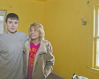 Brandon Sullivan, 15, stands in the bedroom of his home at 157 Logan Ave. SE in Warren with his grandmother, Deborah Nicholl. Earlier this month, Brandon awoke and discovered a fire in the attic where his grandmother was sleeping. He woke her and alerted other family members who got out safely.