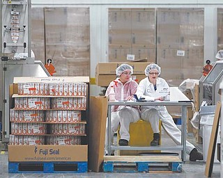 Two employees work in the sleeving plant where labels are put on containers at Chobani Greek Yogurt