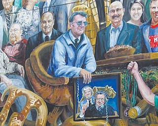 A halo was added Monday above the likeness of legendary Penn State football coach Joe Paterno on the mural outside a student bookstore in State College, Pa.. Paterno died Sunday after a brief battle with lung cancer. He was 85.