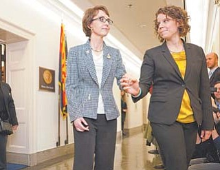 Rep. Gabrielle Giffords, D-Ariz., assisted by her chief of staff, Pia Carusone, leaves her office on Capitol Hill in Washington on Wednesday for the last time as a member of Congress.