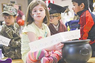 "First-grader Grace Gromada, 7, waits her turn Wednesday to go before the audience at St. Charles School to give the definition of ""rainbow"" at the Boardman school's Vocabulary Parade."