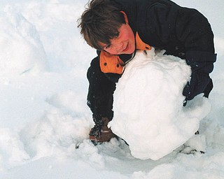 Aaron Hartsough of Canfield is either building a snowman or a really big snowball. Photo sent by Lana VanAuker of Canfield.