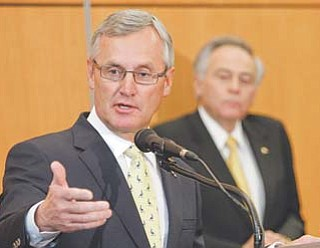 University of Akron president Luis M. Proenza, background, listens as former Ohio State football coach Jim Tressel addresses the media after being introduced as the university's new vice president for strategic engagement at a press conference in Akron on Thursday.