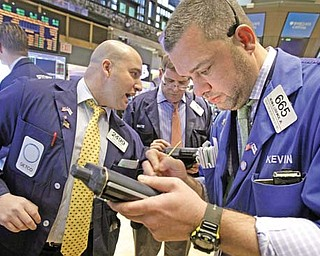 Trader Kevin Lodewick, right, works on the fl oor of the New York Stock Exchange. A strong one-day