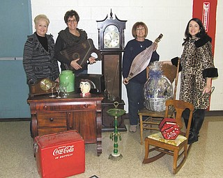 Volunteers for the Junior Group of Goodwill are, from left, Jeri Kurian, Kathy Gerberry, Sue Miller and Laurel Chevlen. They are displaying items to be auctioned off during the 20th annual Junior Group of Goodwill Antique and Collectible Auction on March 3 at Stambaugh Auditorium. The two-day event begins with a gala March 2 that includes a jewelry sale, a live auction, a silent auction and a basket raffle.