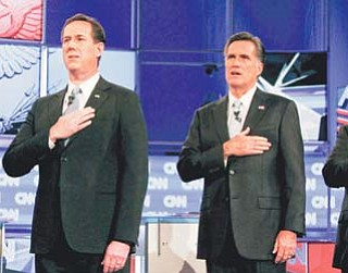 Republican presidential candidates former Pennsylvania Sen. Rick Santorum, left, and former Massachusetts Gov. Mitt Romney stand together for the national anthem before the start of a Republican presidential debate Wednesday in Mesa, Ariz.