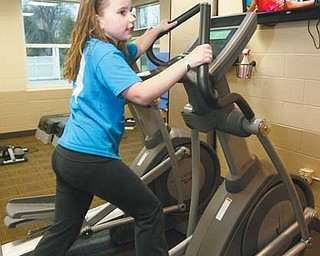 Katelyn Hutton, 9, of Lisbon watches the Disney Channel while using an elliptical at the Children's Fitness Center at the Salem Community Center. The machines are designed for the smaller bodies of the 6-12 age group.
