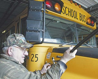 Compressed natural gas vehicles are sparingly used despite an overabundance of the natural resource. Some businesses, however, have begun converting their fleets to CNG. At Lakeview schools in Cortland, the district since the late 1990s has used seven CNG-retrofitted buses. Here, Robert Czako, mechanic, fills a school bus with CNG.