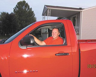 "Jennifer Campman sent this picture of her husband, Dave Campman, and his new truck that he purchased in August 2011. She says it's ""victory"" red, along with the red shirt he is wearing."