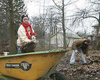 JESSICA M. KANALAS  | THE VINDICATOR..Taylor Benton and her boyfriend, John Moore of Youngstown load garbage and debris into a wheel barrel during a clean-up day held at Blake's home on Lora Ave. The two were standing where his collapsed garage used to lay only a few days ago.
