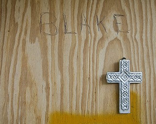 "JESSICA M. KANALAS  | THE VINDICATOR..A cross hangs beneath the words ""BLAKE,"" is written with pen on the wood that covers the hole for Rik's front door."