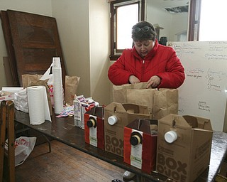 JESSICA M. KANALAS  | THE VINDICATOR..Peggy Gurney of the South side sets out numerous boxes of coffee and dozens of doughnuts donated to the work crew for breakfast.