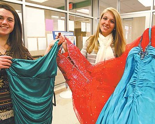 West Branch High School seniors Dottie Schlueter, left, and Mackenzie Shivers show off a few of the prom dresses donated for Project Prom. The program collects used prom dresses and offers them at no charge to high-school girls who need them. The dresses will be available from noon to 4 p.m. March 31 at the Salem Schools administration building, 1226 E. State St.